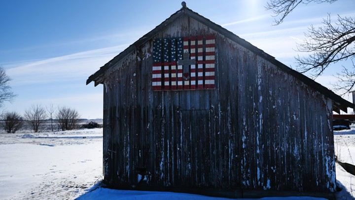A barn in Iowa decorated with an American flag.