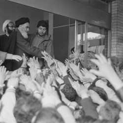 Ayatollah Ruhollah Khomeini greets a crowd of people waving their hands at him at Tehran University in 1979.