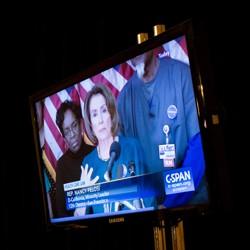 A screen shows Representative Nancy Pelosi, then House minority leader, giving a press conference via C-SPAN.