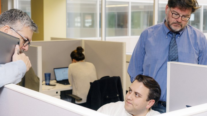 Three male employees of a news website sit and stand in cublcles.
