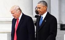 Donald Trump and Barack Obama walk and talk at the U.S. Capitol grounds. A marble pillar can be seen behind them.