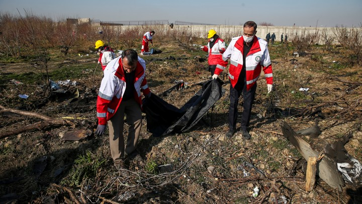 A rescue team carries a body at the site where the Ukraine International Airlines plane crashed after take-off from Iran's Imam Khomeini airport, on the outskirts of Tehran.