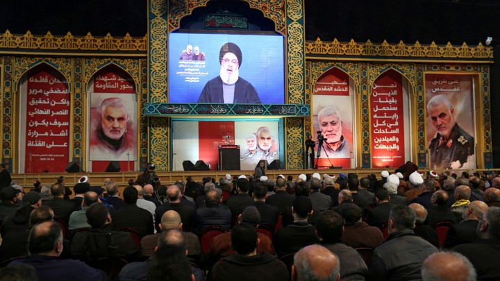 Lebanon's Hezbollah leader Hassan Nasrallah addresses his supporters via a screen during a funeral ceremony rally to mourn Qassem Soleimani.