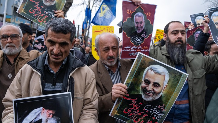 Protesters holding posters of Qassem Suleimani