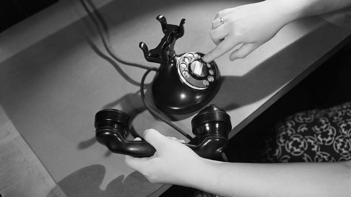A woman's hand dials an antique phone.