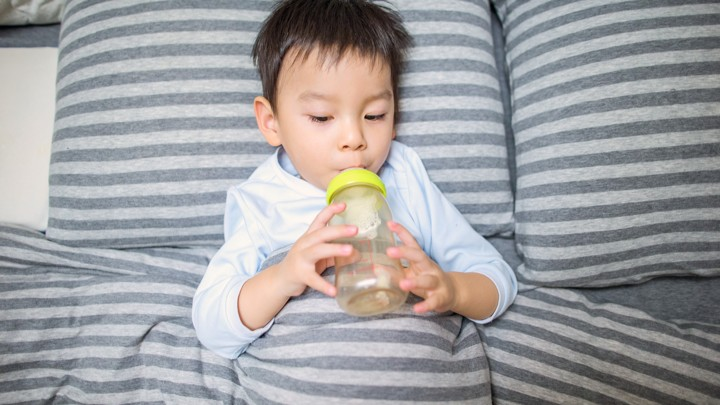 A toddler drinks from a bottle.
