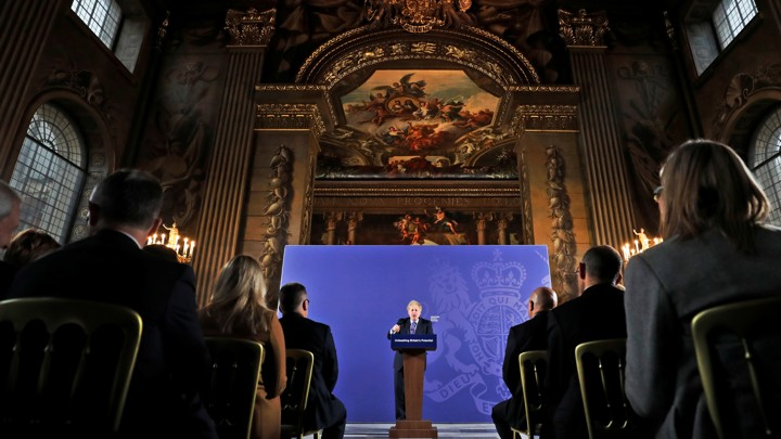 British Prime Minister Boris Johnson gives a speech at the front of an ornate room.