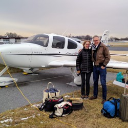 The authors, on a sub-freezing January 2017 morning at the Montgomery County Airpark, in Gaithersburg, Maryland, about to fly toward the west on the final leg of their previous trip. A new journey begins soon. (The yellow cord is to heat the engine sufficiently so it will start.) Around them is all the luggage their Cirrus SR22 would carry, for the next few months on the road.