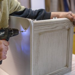 A man drills into wood as he makes furniture