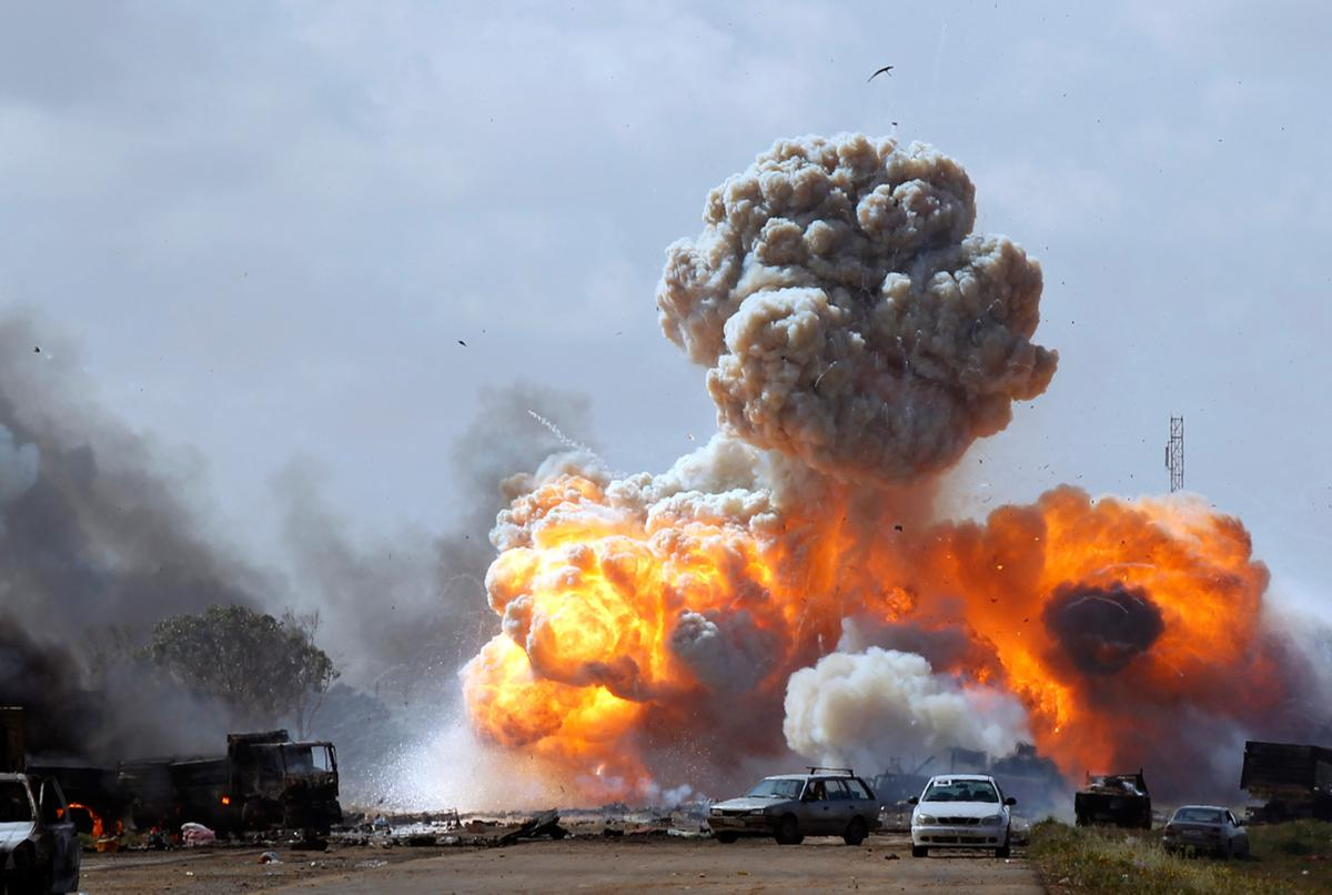 (Vehicles belonging to forces loyal to Libyan leader Muammar Qaddafi explode after an air strike by coalition forces, along a road between Benghazi and Ajdabiyah March 20, 2011 © Reuters/Goran Tomasevic)
