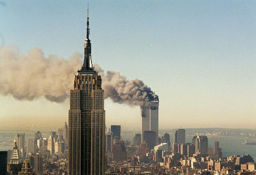 the day of the attacks the atlantic the twin towers of the world trade center burn behind the empire state building in new york on tuesday 11 2001