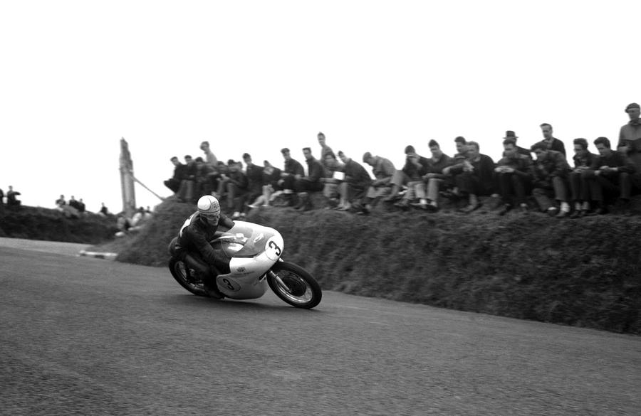 Mike Hailwood, 21, of Oxford, is shown at speed on his Norton motorcycle in the 226-mile Senior International Tourist Trophy Race on the mountain course in ...