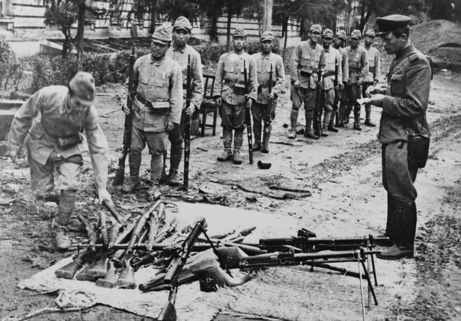 Japanese soldiers surrendering their rifles as a soviet soldier