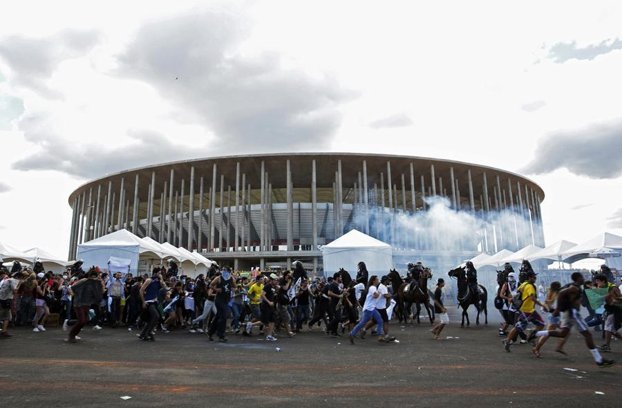 8f90cf508 Activists and students clash with riot police in a cloud of tear gas  outside the Mane Garrincha National Stadium in Brasilia