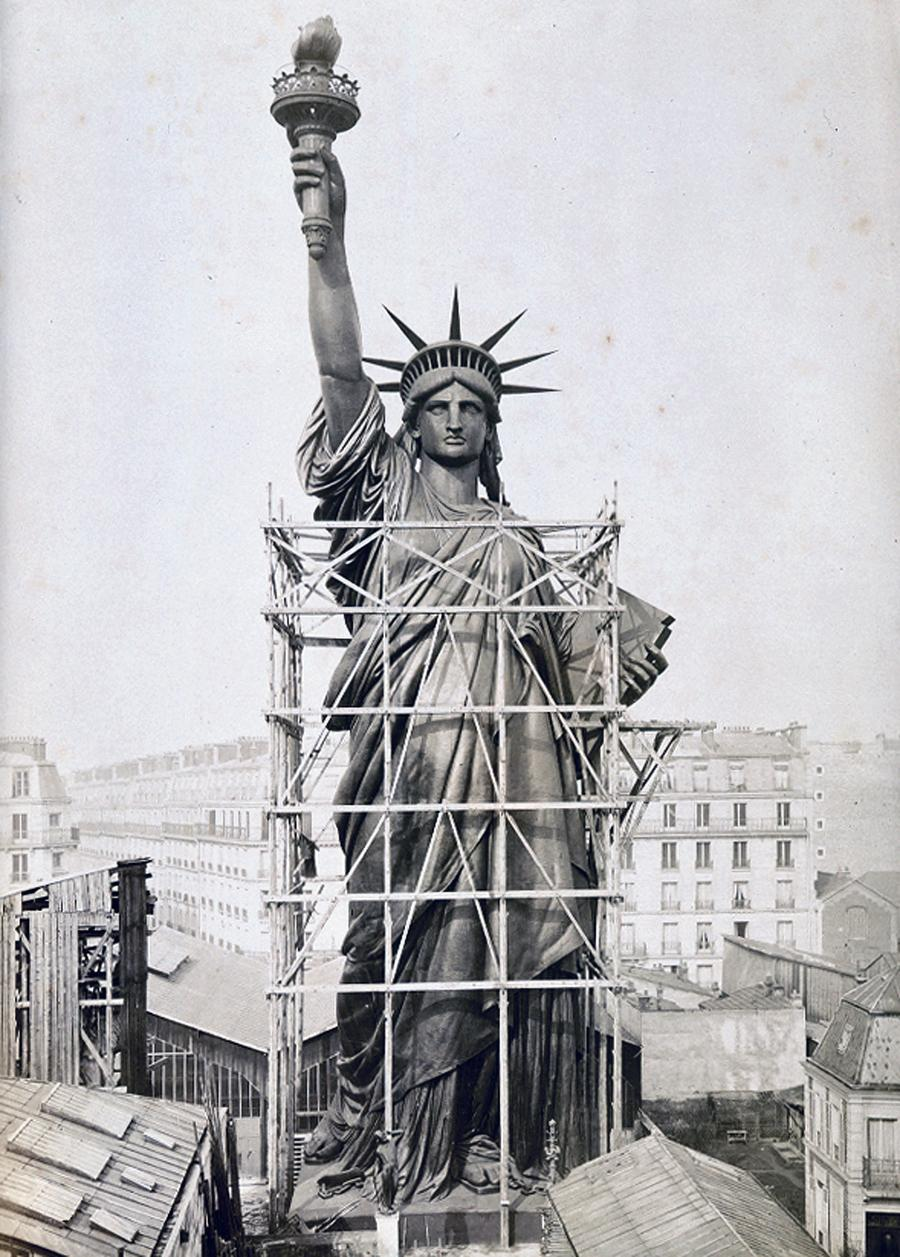 The statue of liberty 127 years at americas gateway the atlantic the statue of liberty towers over paris rooftops in 1884 outside bartholdis workshop buycottarizona Gallery