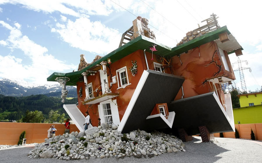 People walk out of an upside down house built by Polish architects Irek  Glowacki and Marek Rozanski, in the western Austrian village of Terfens on  May 5, ...