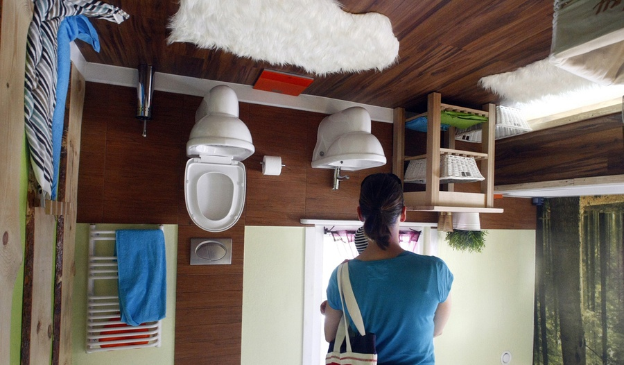A woman stands inside the bathroom of the upside down house in Terfens,  Austria, on May 5, 2012. [Click image to flip view - javascript required] #