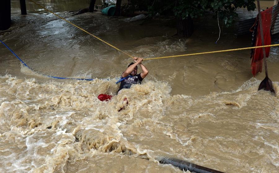 historic flooding in and the atlantic an n kashmiri man uses a rope to cross swift moving floodwater in srinagar on 9 2014 bewildered families nursing children and clutching