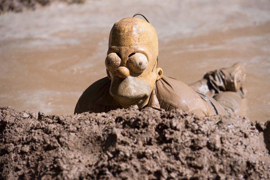 the masks we wear the atlantic a participant of the traditional dirty pig festival wearing a homer simpson mask wallows in a slough near hergisdorf on 25 2015