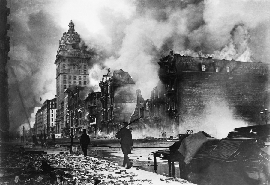 Troops walk east along Market Street after the devastating earthquake of 1906. The Call building burns in the distance. #