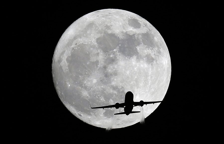 an american airlines passenger plane passes in front of the moon as seen from whittier california on november 13 2017