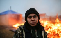 A protestor stands in front of the burning campground at the Standing Rock Sioux reservation in North Dakota.