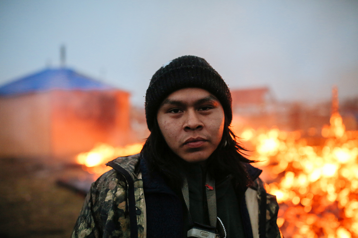 O'Shea Spencer, 20, stands in front of the remains of a hogan structure. Campers set structures on fire in preparation for the Army Corp's 2 p.m. deadline to leave the Oceti Sakowin protest camp on February 22, 2017 in Cannon Ball, North Dakota. Activists and protesters have occupied the Standing Rock Sioux reservation for months in opposition to the completion of the Dakota Access Pipeline.