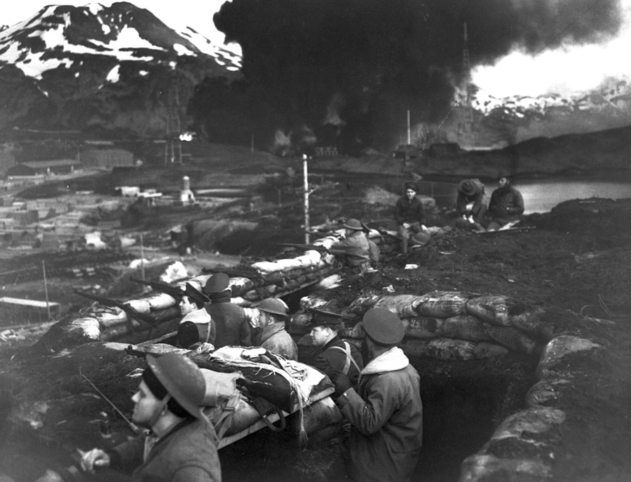 Japanese forces attack Dutch Harbor, Alaska, during World War II, on June  3, 1942. A group of Marines stands on alert between attacks.
