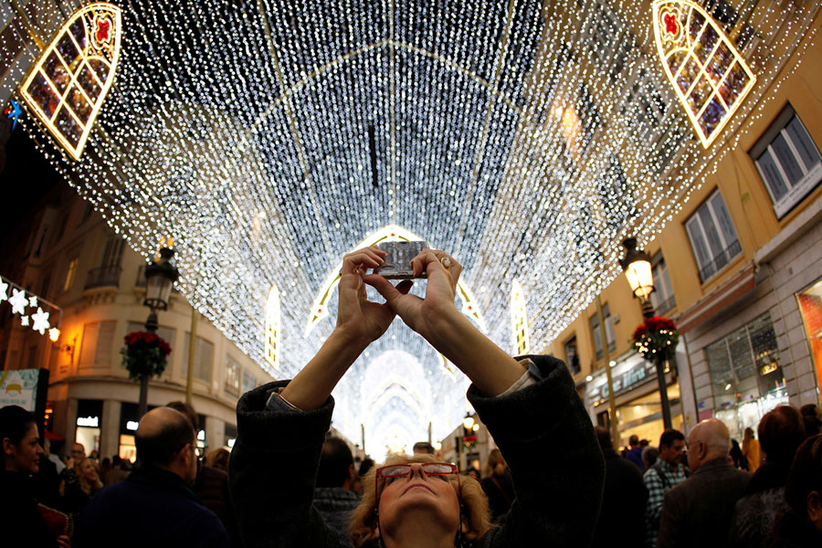 A woman uses a mobile phone to take pictures of Christmas lights during a show of lights and songs to mark the start of the Christmas season at Marqués de ... & Delighting in Holiday Lightshows - The Atlantic azcodes.com