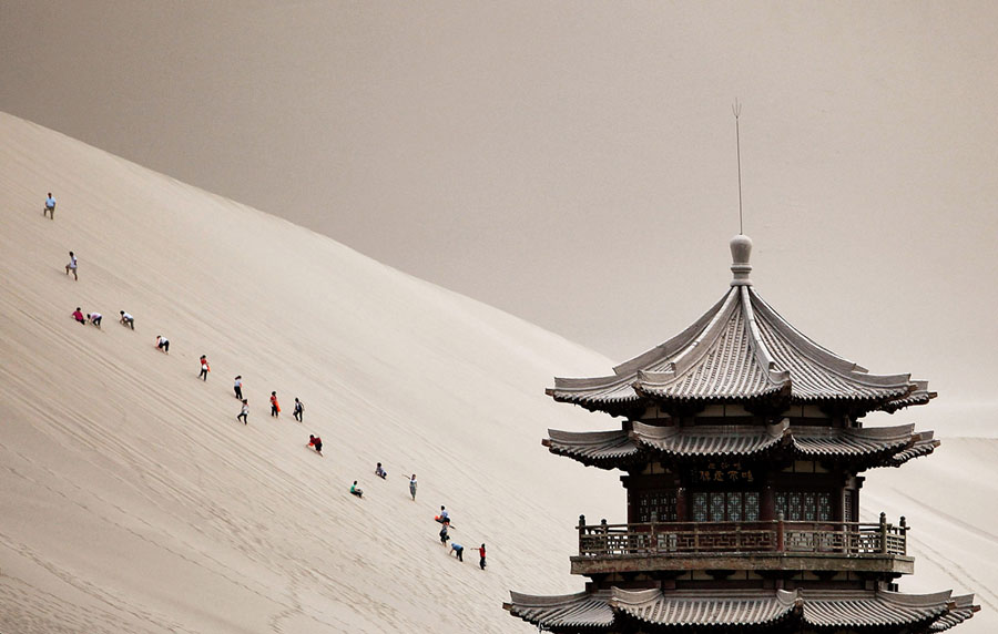Tourists climb Singing Sand Dunes