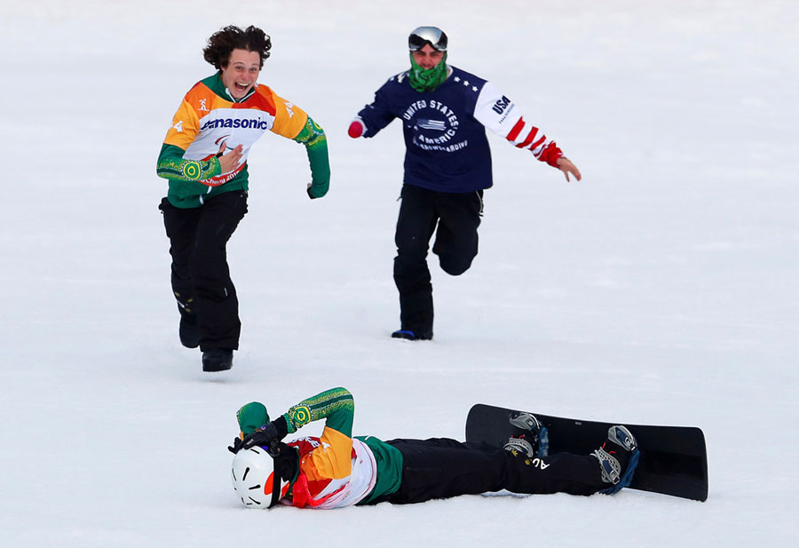 Simon Patmore of Australia lies in the snow after winning the men's snowboard cross SB-UL big final, as fellow competitor Ben Tudhope of Australia rushes to congratulate him on March 12, 2018. # Paul Hanna / Reuters
