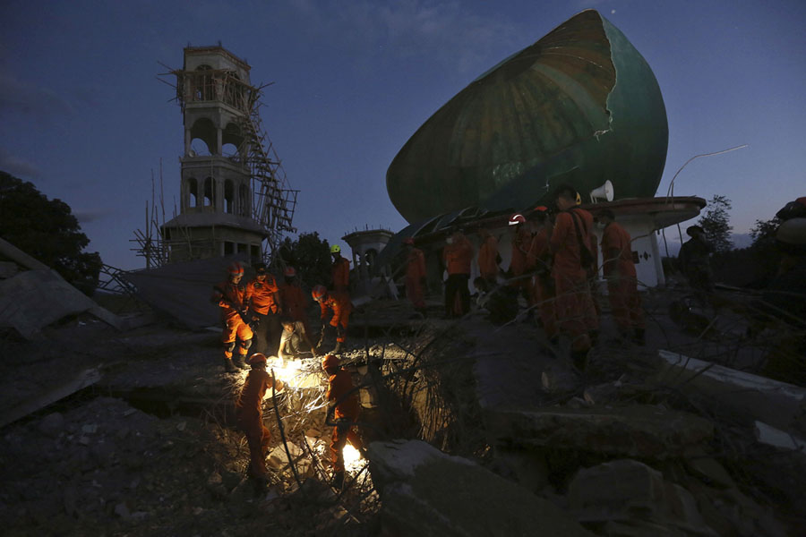 In This August   Photo Rescue Teams Search For Victims In An Earthquake Damaged Mosque In North Lombok Indonesia