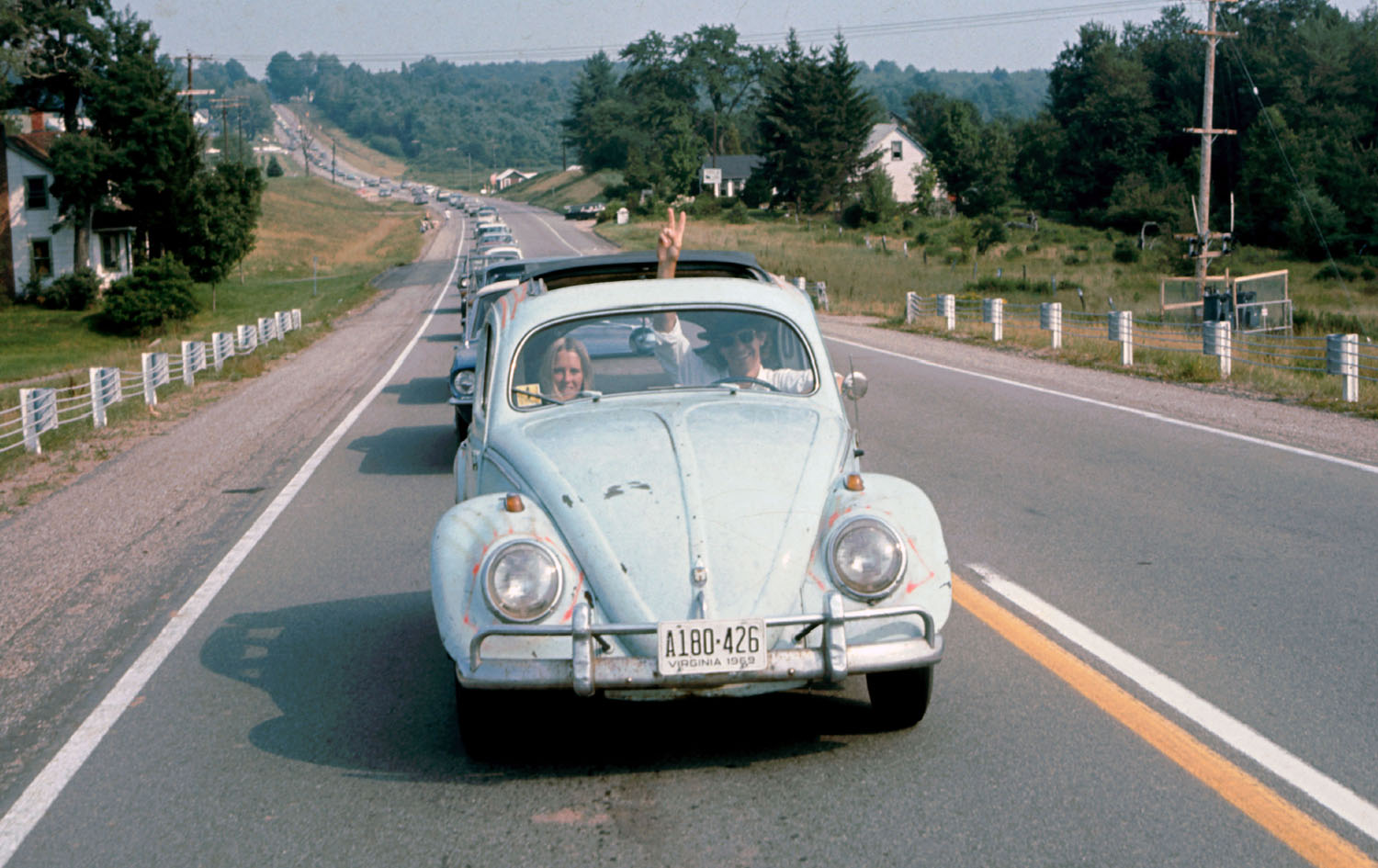 A man drives a Volkswagen Beetle ahead of a long line of cars on the way to the Woodstock Music & Art Fair, while flashing a peace sign through the sunroof of the car, in Bethel, New York, in August 1969. Ralph Ackerman / Getty