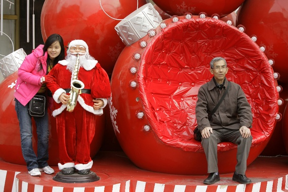 Chinese woman posing with mechanical Santa while older man sits in nearby oversized ornament