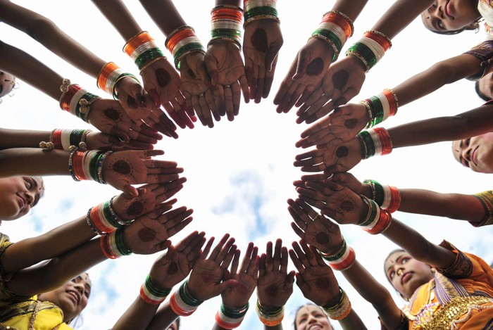 The outstretched hands of Indian girls wearing tricolored bangles form a circle