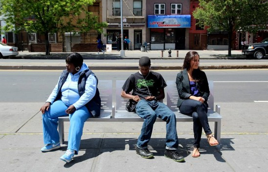 New Yorkers sit on a bench in Harlem