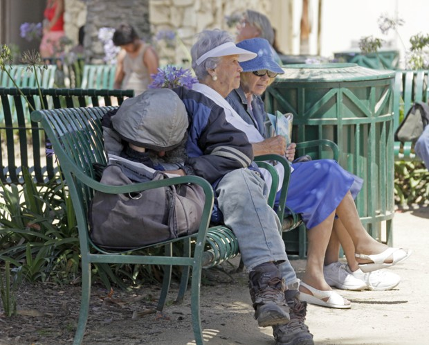 A homeless man and two elderly women share a bench