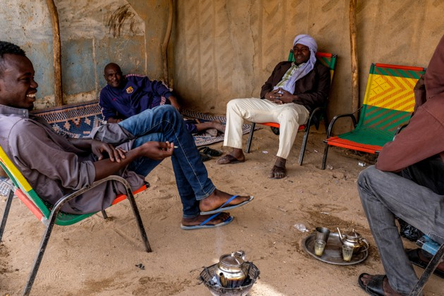 Adou Ama (middle, back), sits under a hangar in downtown Agadez, where he spends his days with other former smugglers drinking tea and smoking cigarettes. / Peter Tinti
