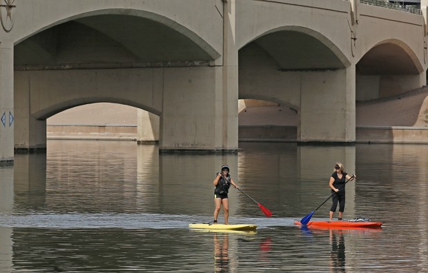 Two paddle boarders row through Tempe Town Lake.