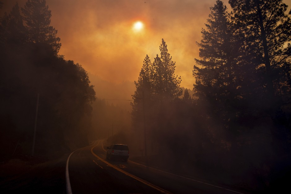 Smoke from nearby wildfires chokes a California roadway.