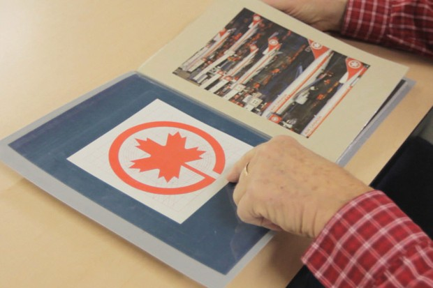 A hand points to a booklet containing the Air Canada logo