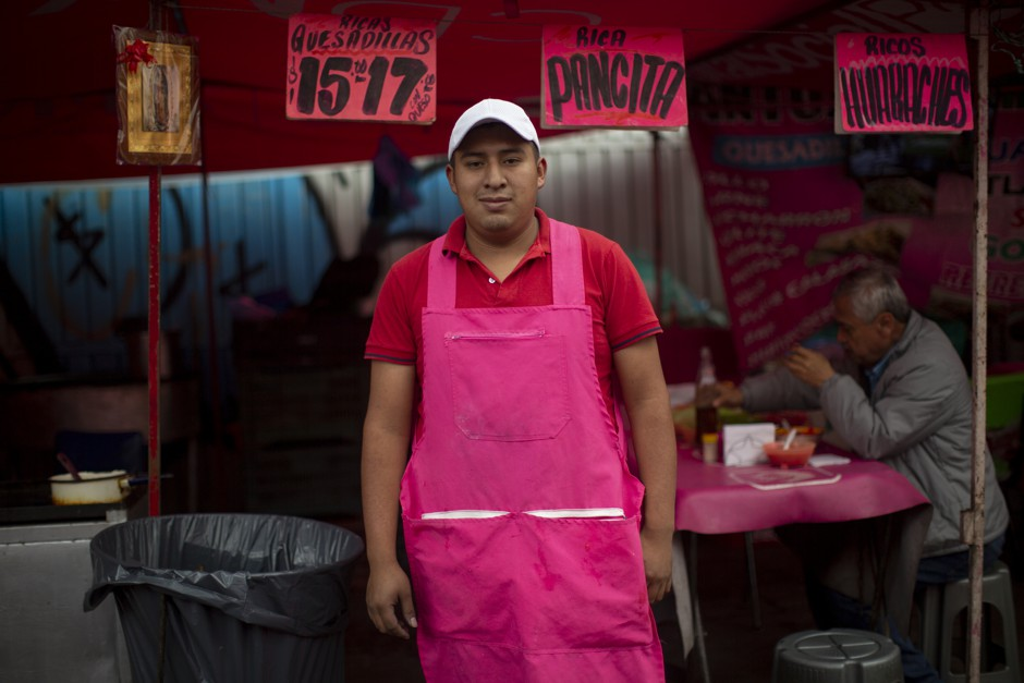 Juan Vargas, owner of a taco, pancita, and quesadilla stands up in an official pink uniform for the public market.