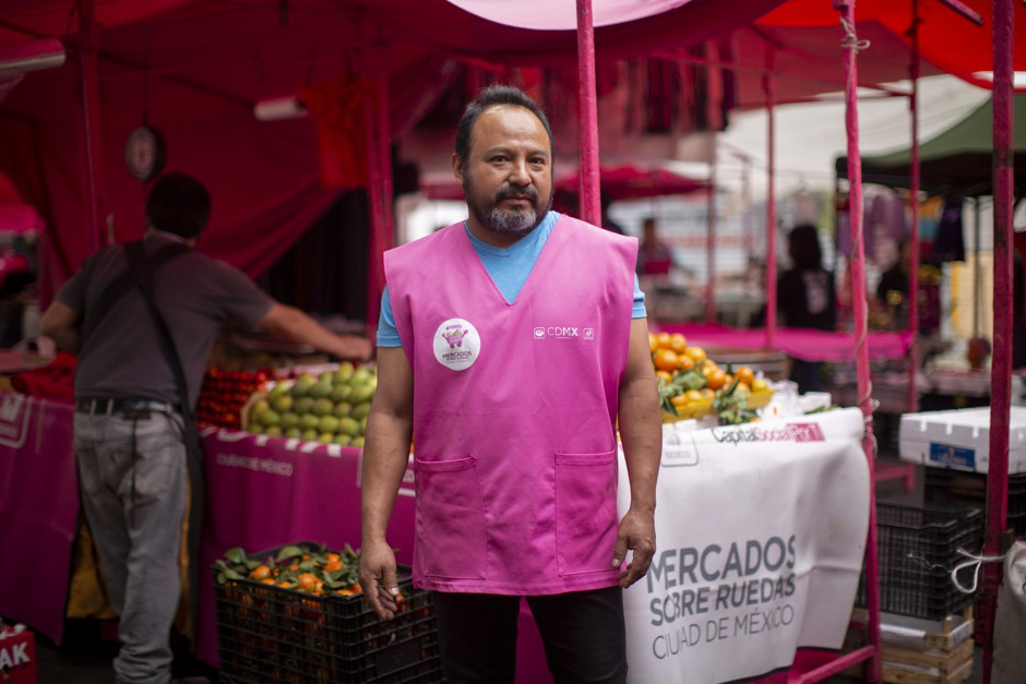 Manuel Gutiérrez poses for a photo in his official pink vest for the public market he works for in Mexico City