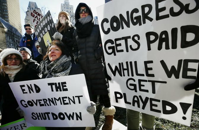 Government workers and their supporters hold signs during a protest in Boston on Friday.