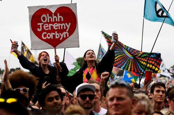 Supporters of Jeremy Corbyn hold up a placard at a music festival.