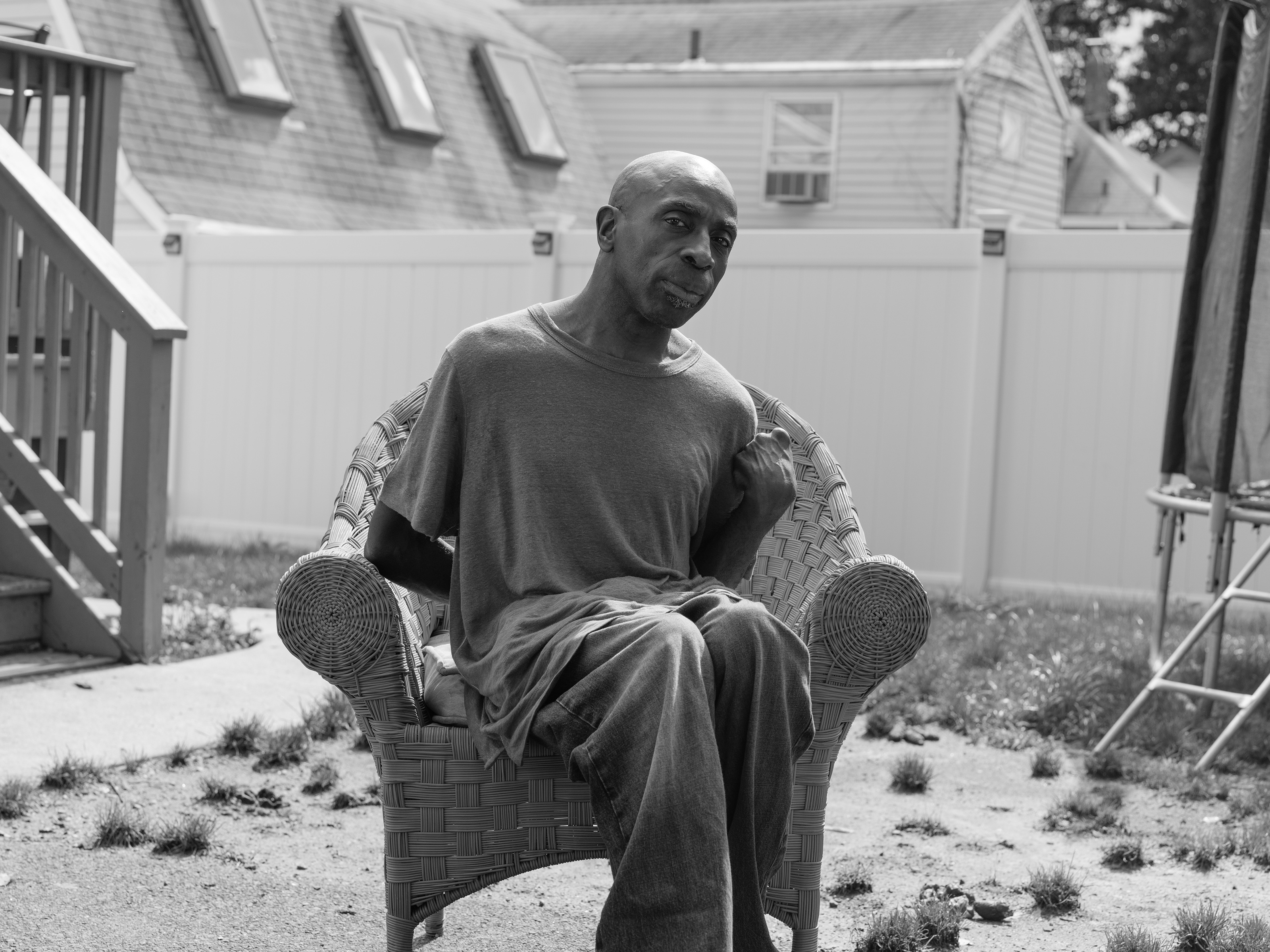 A black and white image of a man sitting in a wicker chair in the sun, in a yard sparsely covered with clumps of grass