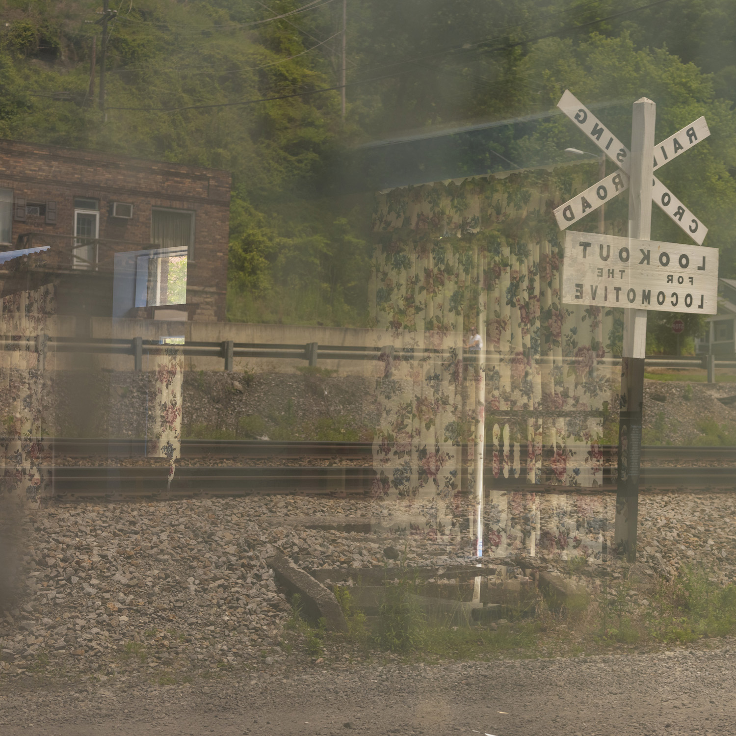 A double exposure of a curtain on a railroad crossing scene