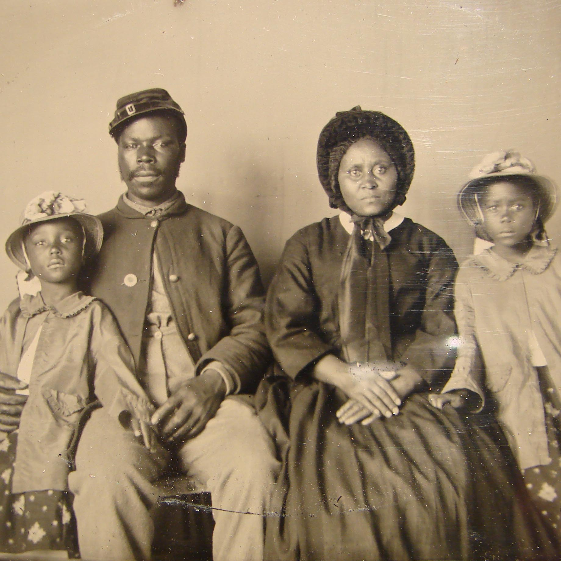 A Black civil war soldier sits with his family for a portrait