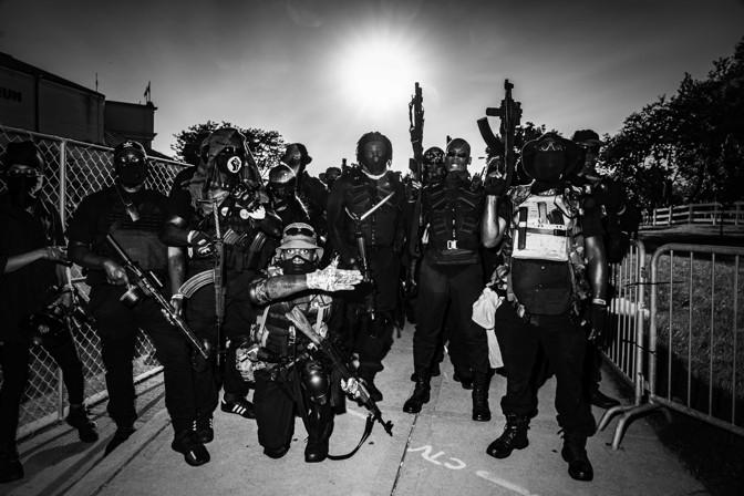 people posing with guns wearing black
