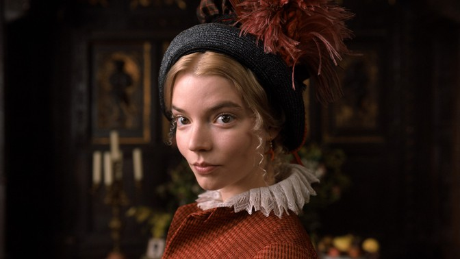 Emma, wearing a feathered bonnet, looks at the camera